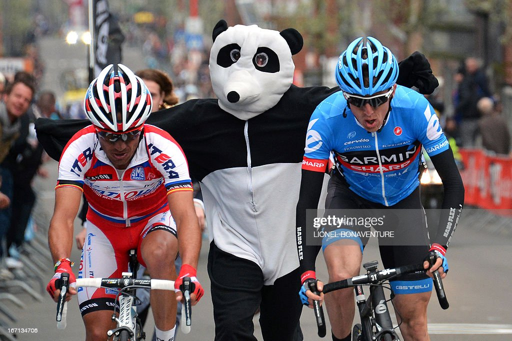 A man dressed as a panda runs near Spain's Joaquim Rodriguez Olivier of the Katusha team (L) and Ireland's Daniel Martin of the Garmin-Sharp team (R) who sprint to win the 99th edition of the Liege-Bastogne-Liege, a 261,5 km one day cycling race, on April 21, 2013, in Liege. Martin won the race ahead of the second-placed Rodriquez and the third-placed Valverde.