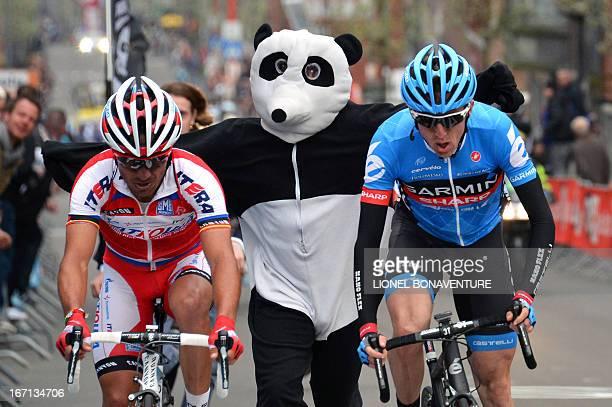 A man dressed as a panda runs near Spain's Joaquim Rodriguez Olivier of the Katusha team and Ireland's Daniel Martin of the GarminSharp team who...
