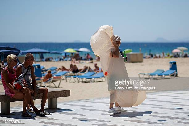 A man dressed as a penis speaks on the phone on Levante Beach on August 10 2013 in Benidorm Spain Benidorm is one of Europe's top package holiday...