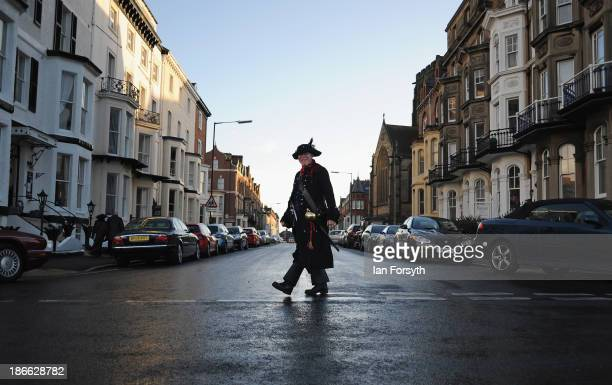 A man dressed as a pirate crosses the street during the Goth weekend on November 2 2013 in Whitby England The Whitby Gothic Weekend that takes place...