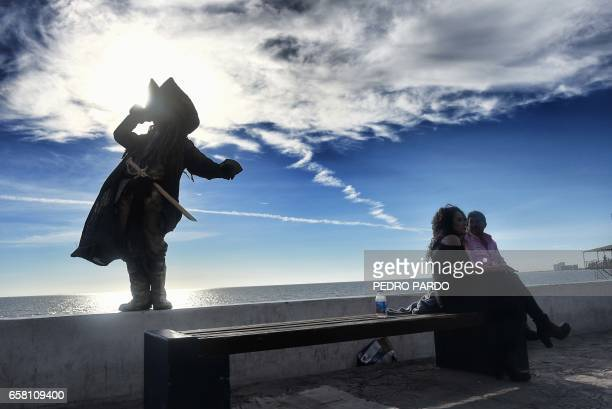 A man dressed as a pirate greets passersby at the Malecon in Puerto Penasco Sonora state Mexico on March 26 2017 / AFP PHOTO / PEDRO PARDO