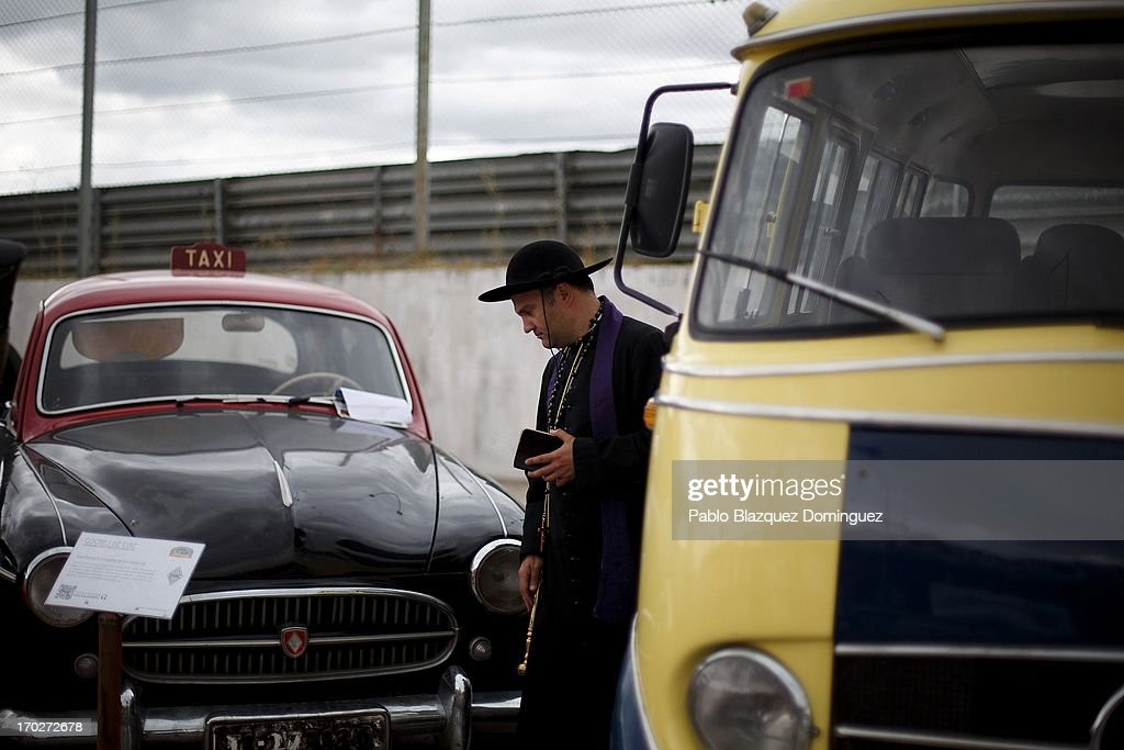 A man dressed as a priest looks at a Taxi Renault Fregate form the 50s at the Jarama Circuit on June 9, 2013 in Madrid, Spain. The Jarama Vintage Festival seeks to revive the 1960s, 70s and 80s attracting classic cars and motorbikes against a background of public orientated activities and shows.