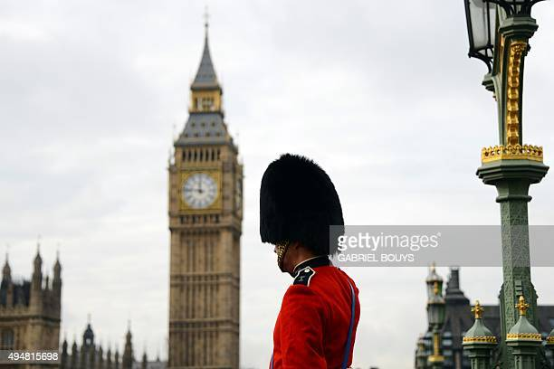 A man dressed as a Queen's Guard welcomes tourists near Big Ben in central London on October 28 2015 AFP PHOTO / GABRIEL BOUYS