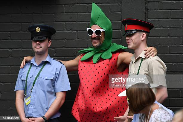 A man dressed as a strawberry poses for a photo with two Military Stewards on day seven of the Wimbledon Lawn Tennis Championships at the All England...