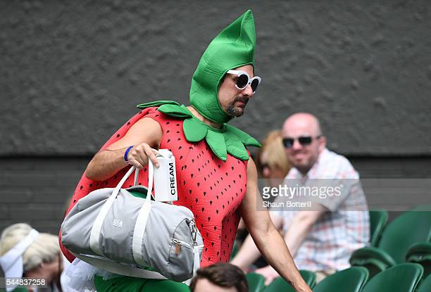 A man dressed as a strawberry watches on from Centre Court on day seven of the Wimbledon Lawn Tennis Championships at the All England Lawn Tennis and...