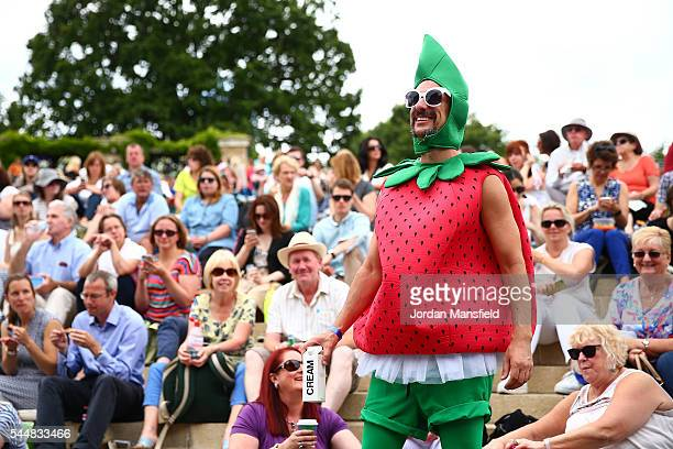 A man dressed as a strawberry watches on from Murray mound on day seven of the Wimbledon Lawn Tennis Championships at the All England Lawn Tennis and...