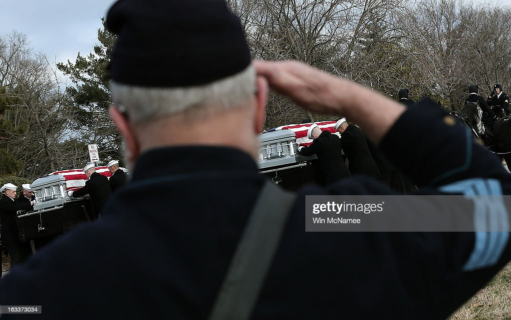 A man dressed as a Union soldier salutes during a funeral service at Arlington National Cemetery as members of a U.S. Navy ceremonial team carry the caskets of two unknown sailors who were killed in 1862 when the Civil War era USS Monitor sank off the coast of North Carolina March 8, 2013 in Arlington, Virgiina. The sailors' remains, recovered when a portion of the ship was raised eleven years ago, were buried with full military honors.