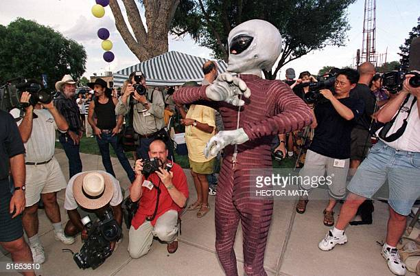 A man dressed as an alien is surrounded by reporters during a costume competition in downtown Roswell 03 July Roswell is celebrating the 50th...