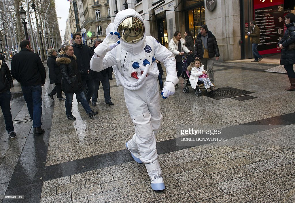 A man dressed as an astronaut walks down the Champs-Elysees avenue in Paris, on January 4, 2013.