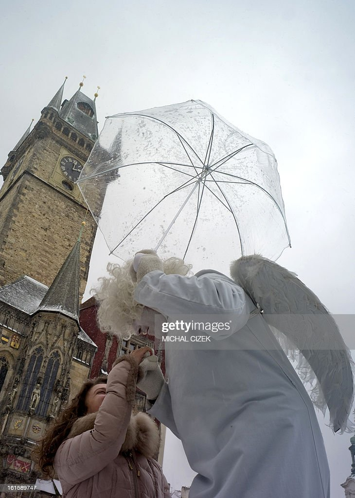 A man dressed as angel poses with an unbrella and a tourist during a snowfall on February 12, 2013 at the Old Town Square in Prague.