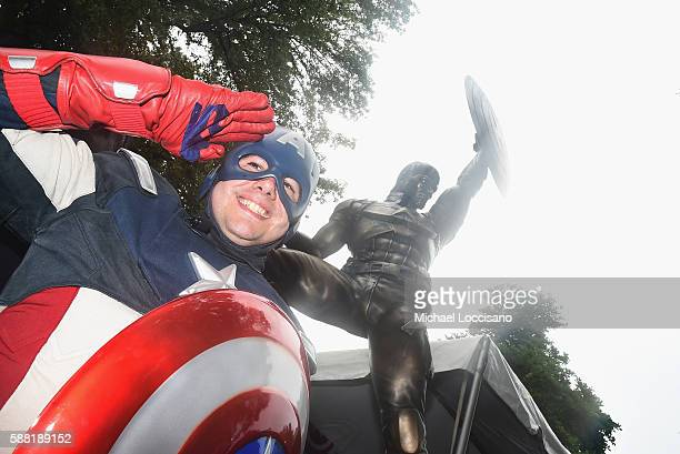 A man dressed as Captain America poses in front of the statue of Captain America during the statue dedication ceremony at Prospect Park on August 10...