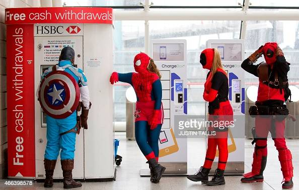 A man dressed as Captain America poses withdrawing cash from a cash point next to other visitors dressed as Spider Woman Lady Deadpool and Assassin...
