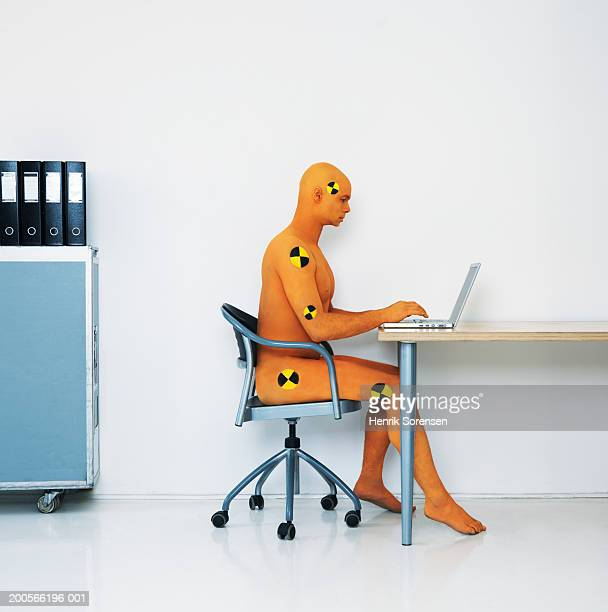 Man dressed as crash test dummy using laptop at desk, side view