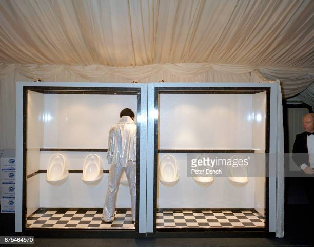 A man dressed as Elvis uses the temporary toilet at the Systems Union Las Vegasthemed Christmas party in a marquee in Farnborough November 2002