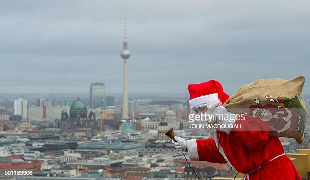 A man dressed as Father Christmas aka Santa Claus waves to people from the top of the Kollhoff tower in front of a Berlin skyline on December 13 2015...