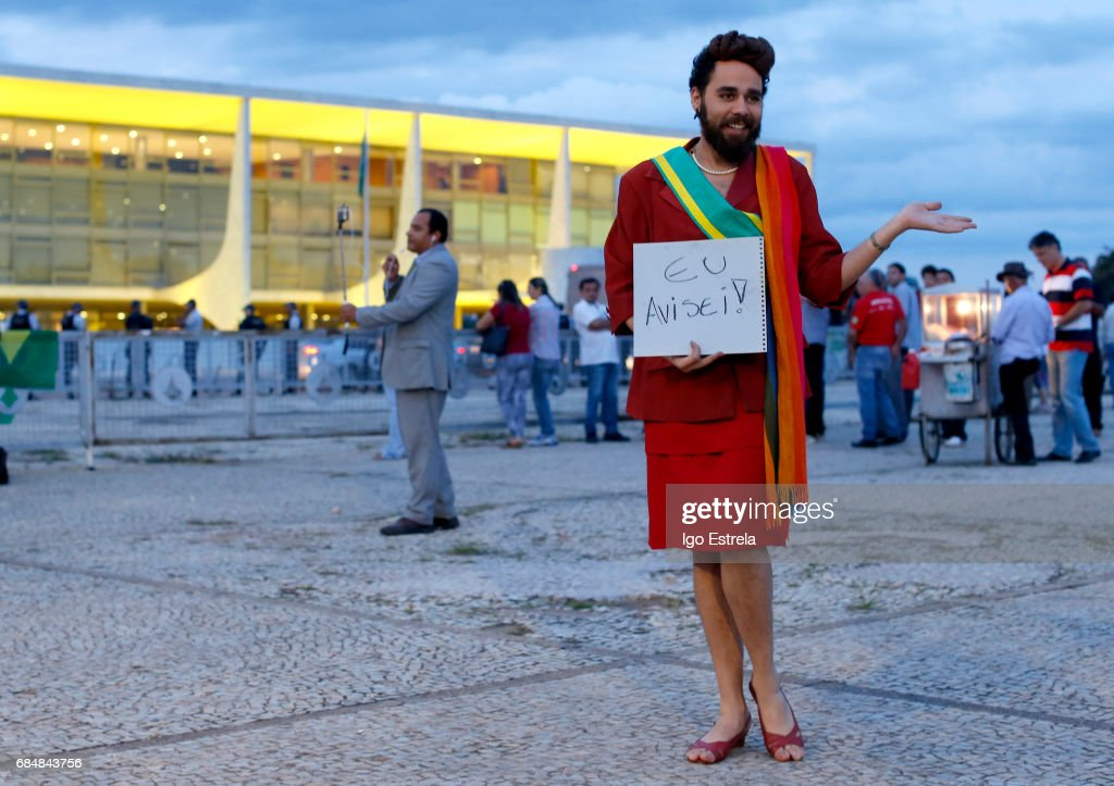 A man dressed as former President Dilma Rousseff carries a sign that says 'I warned you' as protests erupt after embattled President Temer refuses to resign on May 18, 2017 in Brasilia, Brazil. A recording of Temer was released in which he allegedly condones bribery payments to Eduardo Cunha, the former President of the Chamber of Deputies. Cunha was involved in the 'Lava Jato' (Car Wash) corruption scandal and sentenced to 15 years in prison after being found guilty of corruption, money laundering and illegal money transfers abroad. With the release of the recording, the opposition has called for Temer's impeachment and new elections.