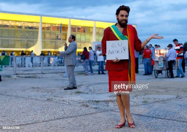 A man dressed as former President Dilma Rousseff carries a sign that says 'I warned you' as protests erupt after embattled President Temer refuses to...
