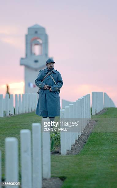 A man dressed as French soldier of the First World War walks during a dawn service at the Australian War Memorial in the northern French city of...
