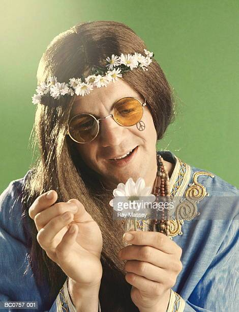 Man dressed as 'hippy', contemplating daisy, close-up