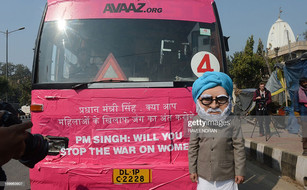 A man dressed as Indian Prime Minister Manmohan Singh stands in front of the 'Pink Bus' which launched the Campaign for Education as the solution to cure India's rape epidemic at Munirka Bus stand in New Delhi on January 24, 2013. After one month of lurid reporting on a horrifying gang-rape and murder of a student in a bus by five men in New Delhi, women in the Indian capital say they are not safe in Delhi. AFP PHOTO/RAVEENDRAN