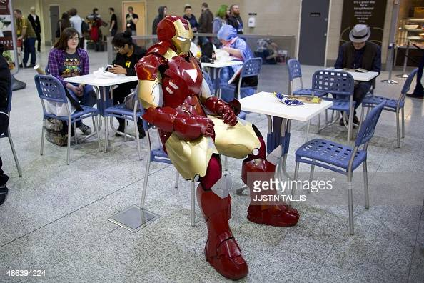 A man dressed as Ironman takes a seat in the cafeteria on the second day of the London Super Comic Convention at the ExCel centre in east London on...