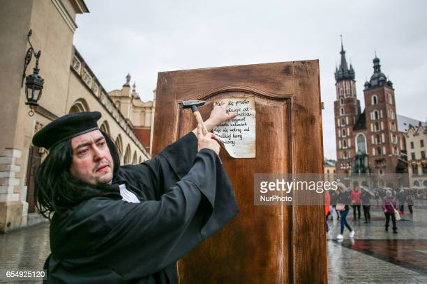 A man dressed as Martin Luther nails a copy of ' 95 Theses ' to the door at the Main Square in Krakow Poland on 18 March 2017 A happening was...