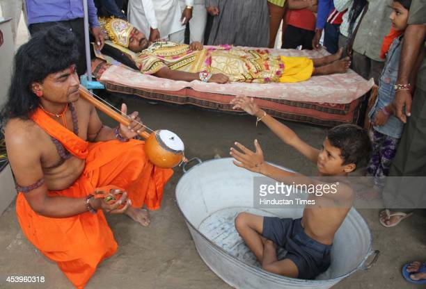 A man dressed as Narad tries to wake up Indra god of rain as achild sits in an empty vessel as a part of superstition to invoke rain god on August 22...