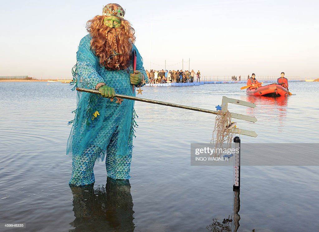 A man dressed as Neptun is pictured in the waters of the North Sea on January 1, 2014 in Butjadingen as part of the New Year's swim.