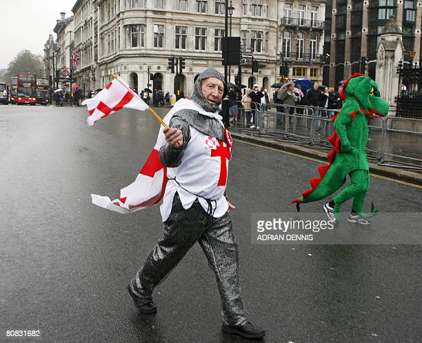 A man dressed as Saint George crosses the road beside a man dressed as a dragon outside the Houses of Parliament in London on April 23 2008 The act...