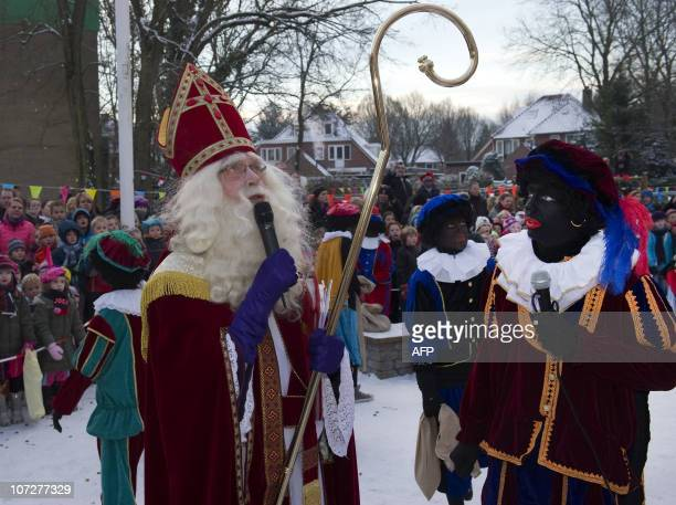 A man dressed as Saint Nicholas talks next to his Black Peters during a celebration in a primary school on December 3 2010 in Soest Sinterklaas feast...