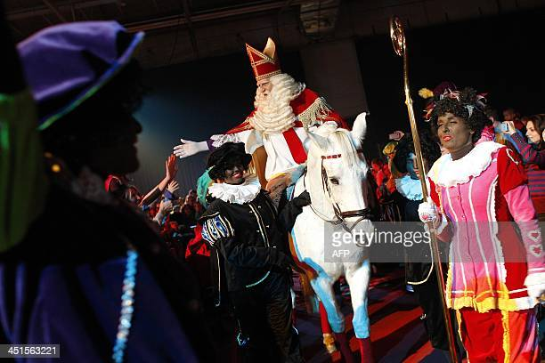A man dressed as Saint Nicnolas rides a horse next to women dressed as Black Petes as they arrive for the 'Club of Saint Nicolas Party Tour' at the...