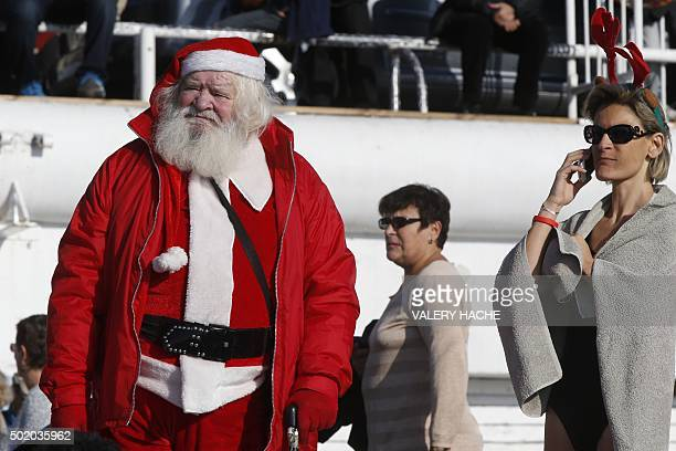 A man dressed as Santa Claus attends the traditional Christmas bath on December 20 2015 on the beach of the French riviera city of Nice southeastern...