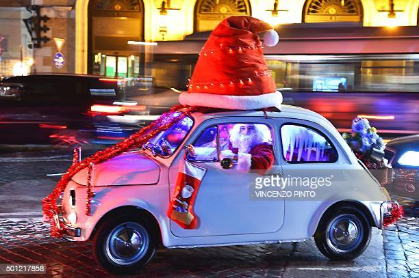 A man dressed as Santa Claus drives an old Fiat 500 car at Piazza Venezia square in central Rome on December 13 2015 AFP PHOTO / VINCENZO PINTO / AFP...