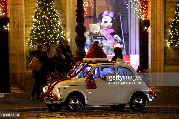 A man dressed as Santa Claus drives his old Fiat 500 in the Piazza Venezia in central on December 23 as people prepare for Christmas AFP PHOTO /...