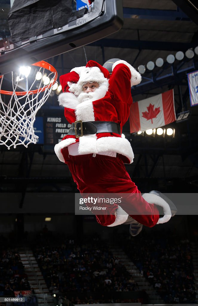 A man dressed as Santa Claus dunks during the game between the New York Knicks and Sacramento Kings on December 10 2015 at Sleep Train Arena in...