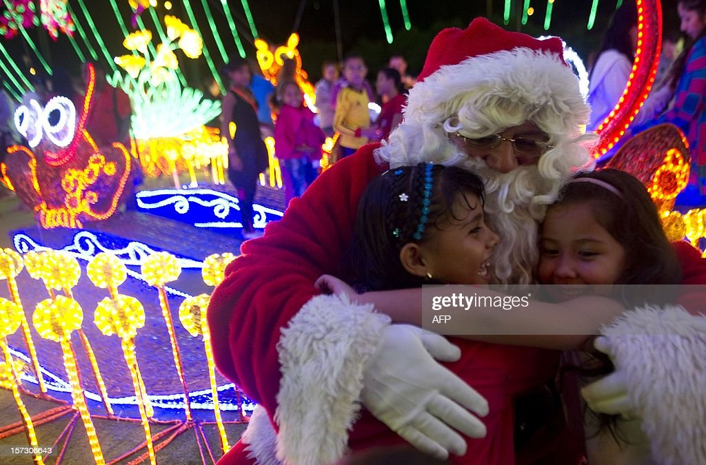 Man dressed as Santa Claus embraces girls during the Christmas lights illumination in the Medellin river on December 1, 2012 in Medellin, Antioquia department, Colombia. AFP PHOTO/Raul ARBOLEDA