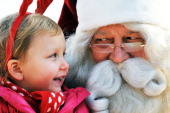 A man dressed as Santa Claus from Lapland Finland listens to a girl's Christmas wish on stage at a Christmas event organised by the Finnish embassy...