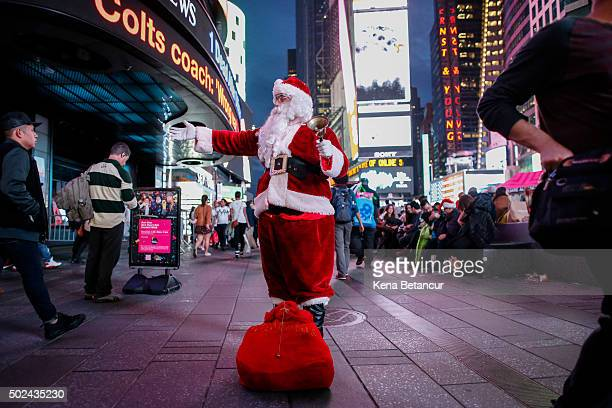 A man dressed as Santa Claus greets people in Times Square on December 24 2015 in New York City Lastminute shoppers get some of the best deals many...