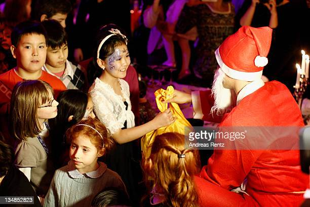 A man dressed as Santa Claus hands over gifts to childs of the diplomatic corp during the St Nicolas Day Brunch 2011 charity party at Palazzo on...