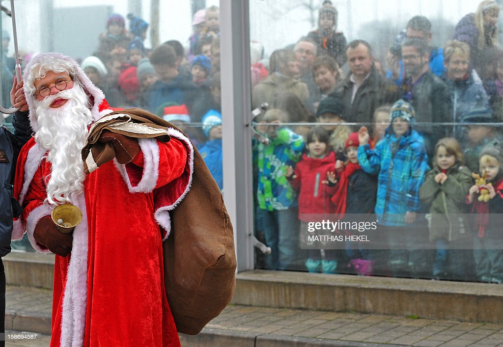 A man dressed as Santa Claus is welcomed by children after arriving with his Christmas Air flight from Lapland at the airport in Dresden, eastern Germany, on December 24, 2012.