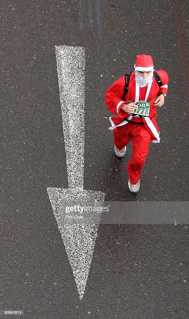 A Man dressed as Santa Claus runs under Waterloo Bridge during the 2008 Flora London Marathon on April 13, 2008 in London, England.