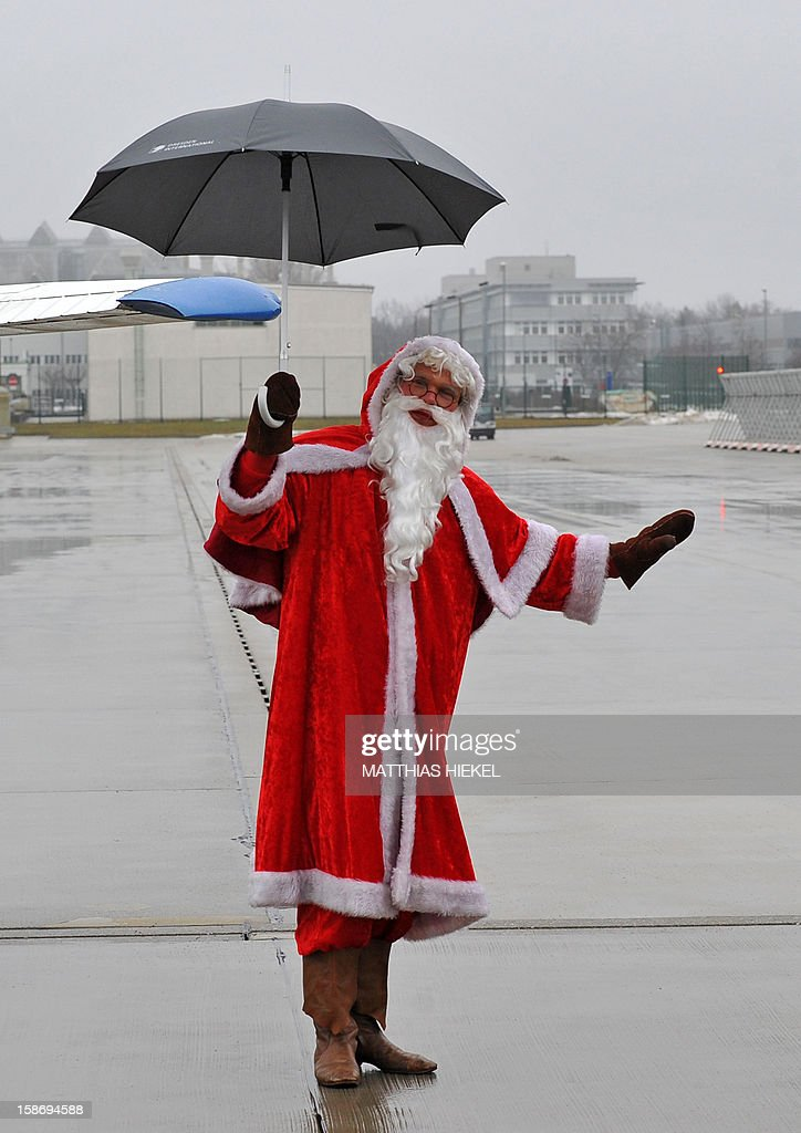A man dressed as Santa Claus uses an umbrella after arriving with his Christmas Air flight from Lapland at the airport in Dresden, eastern Germany, on December 24, 2012.