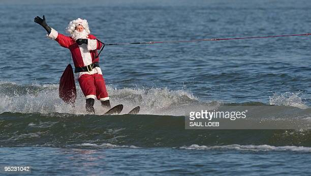 A man dressed as Santa Claus water skis on the Potomac River at National Harbor in Prince George's County Maryland near Washington DC on December 24...