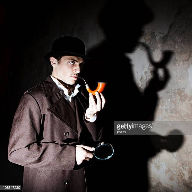 A man dressed as Sherlock Homes, with moody lighting