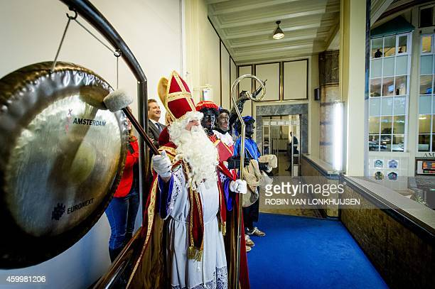 A man dressed as Sinterklaas aka Saint Nicholas visits the Amsterdam Stock Exchange to beat the gong in Amsterdam The Netherlands on December 5 2014...