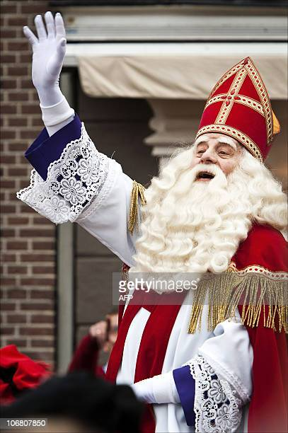 A man dressed as Sinterklaas or Saint Nicholas waves to children after his arrival by boat in the harbour of Hardewijk on November 13 2010 The...