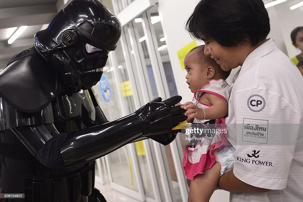 A man dressed as the character Dark Trooper from a famous movie Star Wars plays with a kid during the Star Wars day in Bangkok, Thailand on May 4, 2016.