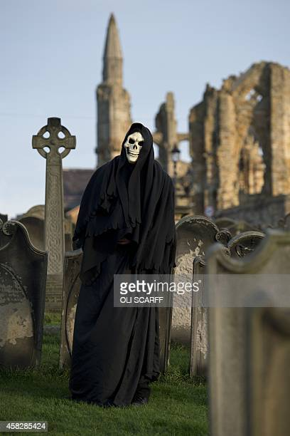 A man dressed as the Grim Reaper poses for pictures during the biannual 'Whitby Goth Weekend' festival in Whitby Northern England on November 2 2014...