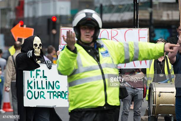 A man dressed as the Grim Reaper takes part in a demonstration by taxi drivers in central London on May 26 against mobile app Uber and regulator...