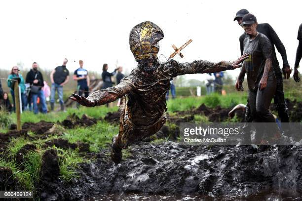 A man dressed as the Pope jumps into a pool of mud as competitors take part in the annual McVities Mud Madness 8km cross country run on April 9 2017...